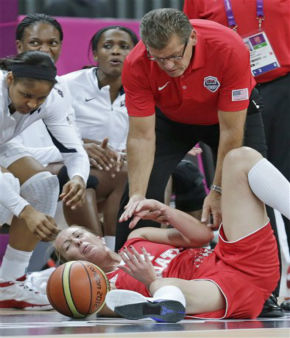 USA head coach Geno Auriemma, top, helps up Croatia guard Sandra Mandir after she was knocked out of bounds during a basketball game at the 2012 Summer Olympics, Saturday, July 28, 2012, in London. &#40;AP Photo&#47;Charles Krupa&#41; <span class=meta>(AP Photo&#47; Charles Krupa)</span>