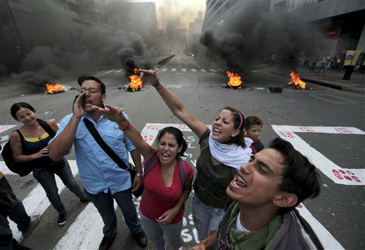University students shout slogans against Venezuela&#39;s Education Minister Pedro Calzadilla near a burning road block they set up in the Chacao neighborhood of Caracas, Venezuela, Thursday, July 11, 2013. Students are demanding an increase in the budget of public universities nationwide. &#40;AP Photo&#47;Fernando Llano&#41; <span class=meta>(AP Photo&#47; Fernando Llano)</span>