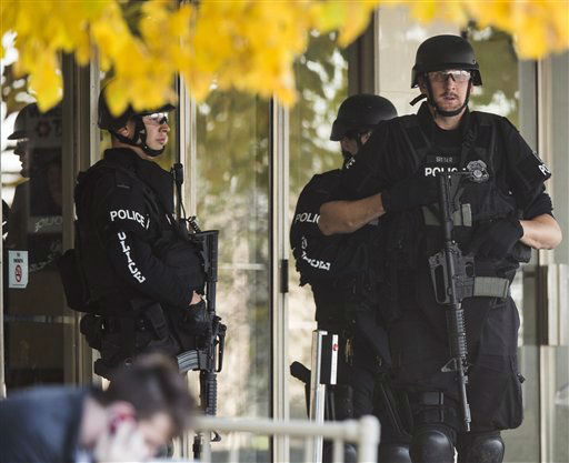 Police stand with guns drawn at the entrance to Brookfield Square Mall across from the scene of a shooting at Azana Salon in Brookfield, Wis. on Sunday , Oct. 21, 2012.  Police identified the shooting suspect as Radcliffe Franklin Haughton, 45, of Brown Deer, Wis.  Brookfield Police Chief Dan Tushaus said Haughton&#39;s car had been found, but he was still at large. Three people have been killed and four others have been wounded.   &#40;AP Photo&#47;Tom Lynn&#41; <span class=meta>(AP Photo&#47; Tom Lynn)</span>