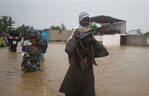 A man carries a child as residents leave an area flooded by Tropical Storm Isaac in Port-au-Prince, Haiti, Saturday, Aug. 25, 2012. Tropical Storm Isaac swept across Haiti&#39;s southern peninsula early Saturday, dousing a capital city prone to flooding and adding to the misery of a poor nation still trying to recover from the 2010 earthquake. &#40;AP Photo&#47;Dieu Nalio Chery&#41; <span class=meta>(AP Photo&#47; Dieu Nalio Chery)</span>