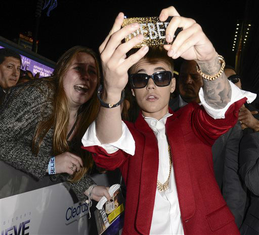Singer Justin Bieber takes a photo with a fan at the premiere of the feature film &#34;Justin Bieber&#39;s Believe&#34; at Regal Cinemas L.A. Live on Wednesday, Dec. 18, 2013, in Los Angeles. &#40;Photo by Dan Steinberg&#47;Invision&#47;AP&#41; <span class=meta>(Photo&#47;Dan Steinberg)</span>