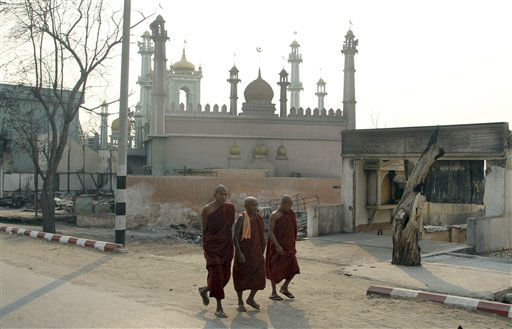 Three Buddhist monks walk on a road near a mosque in Meikhtila, about 550 kilometers &#40;340 miles&#41; north of Yangon, Myanmar, Monday, March 25, 2013. Sectarian clashes between Buddhists and Muslims in Myanmar spread to at least two other towns in the country&#39;s heartland over the weekend, undermining government efforts to quash an eruption of violence that has killed dozens of people and displaced 10,000 more. On Sunday, Vijay Nambiar, the U.N. secretary-general&#39;s special adviser on Myanmar, toured Meikhtila, where soldiers were able to impose order after several days of anarchy and called on the government to punish those responsible. &#40;AP Photo&#47;Khin Maung Win&#41; <span class=meta>(AP Photo&#47; Khin Maung Win)</span>