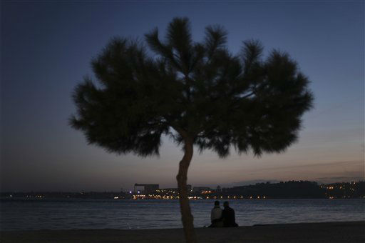 A couple sit by the Tagus river bank at sunset in Lisbon, Monday, Jan. 28, 2013. &#40;AP Photo&#47;Francisco Seco&#41; <span class=meta>(AP Photo&#47; Francisco Seco)</span>