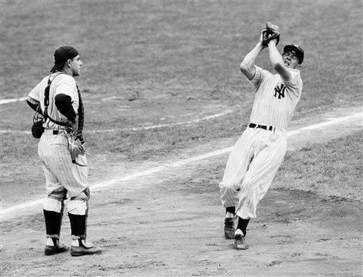 FILE - In this July 16, 1954, file photo, New York Yankees third baseman Andy Carey catches pop fly by Baltimore&#39;s Jim Fridley as Yankees catcher Yogi Berra watches during a baseball game in New York. Carey, third baseman for the Yankees dynasty of the 1950s that won four straight American League pennants and two World Series, has died at 80. Daughter Elizabeth Carey tells the New York Times he died Dec. 15, 2011, in California of Lewy body dementia. &#40;AP Photo&#47;John Rooney, File&#41; <span class=meta>(AP Photo&#47; John Rooney)</span>