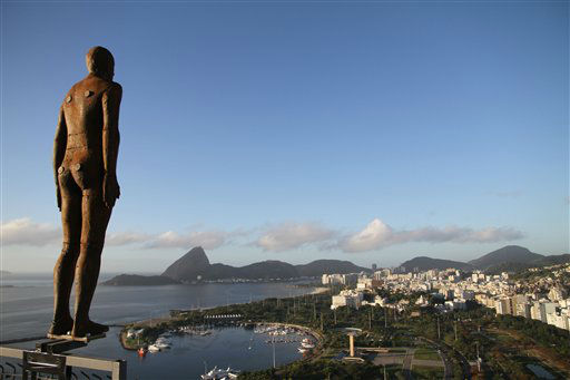 A sculpture by British artist Antony Gormley is displayed on the edge of a building in front of the Sugar Loaf mountain at the Guanabara bay, in Rio de Janeiro, Brazil, Thursday, Aug. 16, 2012. The Still Being exhibition is located in Rio de Janeiro downtown, and brings sculptures in the shape of men made of iron and full-scale. Placed singly at the top of the buildings, quietly they transform the urban landscape of the region. &#40;AP Photo&#47;Renata Brito&#41; <span class=meta>(AP Photo&#47; Renata Brito)</span>