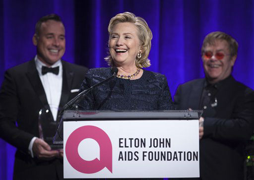 Former Secretary of State Hillary Clinton speaks as Elton John &#40; R&#41; and his partner David Furnish &#40;L&#41; look on, after receiving her Founders award during the Elton John AIDS Foundation&#39;s 12th Annual &#34;An Enduring Vision&#34; benefit gala at Cipriani Wall Street on Tuesday, Oct. 15, 2013 in New York. &#40;Photo by Carlo Allegri&#47;Invision&#47;AP&#41; <span class=meta>(Photo&#47;Carlo Allegri)</span>