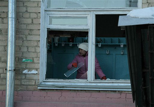 In this photo provided by Chelyabinsk.ru a woman cleans away glass debris from a window after a meteorite explosion over Chelyabinsk region on Friday, Feb. 15, 2013. A meteor exploded in the sky above Russia on Friday, causing a shockwave that blew out windows injuring hundreds of people and sending fragments falling to the ground in the Ural Mountains.  The Russian Academy of Sciences said in a statement hours after the Friday morning fall that the meteor entered the Earth&#39;s atmosphere at a speed of at least 54,000 kph &#40;33,000 mph&#41; and shattered about 30-50 kilometers &#40;18-32 miles&#41; above ground. The fall caused explosions that broke glass over a wide area. &#40;AP Photo&#47; Yevgenia Yemelyanova, Chelyabinsk.ru&#41; <span class=meta>(AP Photo&#47; Yevgenia Yemelyanova)</span>