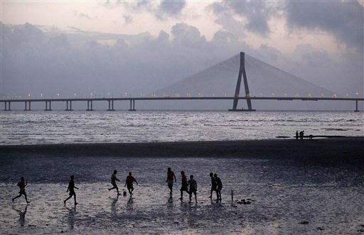With the Bandra?Worli Sea Link in the background, men play football on the sea shore in Mumbai, India, Saturday, Aug. 18, 2012. (AP Photo/Rajanish Kakade)