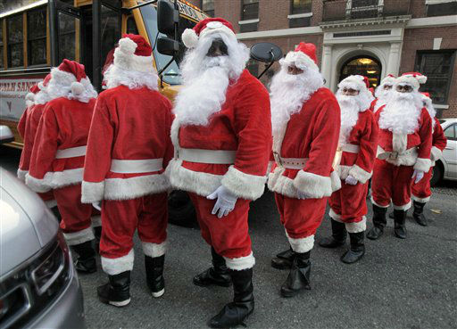 Volunteers of America Santas board a school bus to the start of the 110th annual Sidewalk Santa Parade, in New York,  Friday, Nov. 23, 2012. The donations they raise are used for a holiday food voucher program for needy residents. &#40;AP Photo&#47;Richard Drew&#41; <span class=meta>(AP Photo&#47; Richard Drew)</span>