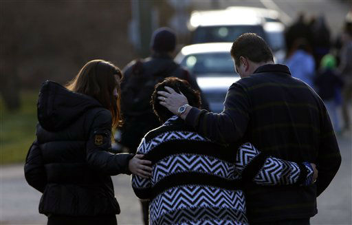 A woman is comforted after paying her respects at a memorial for shooting victims near Sandy Hook Elementary School, Saturday, Dec. 15, 2012 in Newtown, Conn.  A gunman walked into Sandy Hook Elementary School in Newtown Friday and opened fire, killing 26 people, including 20 children. &#40;AP Photo&#47;Jason DeCrow&#41; <span class=meta>(AP Photo&#47; Jason DeCrow)</span>