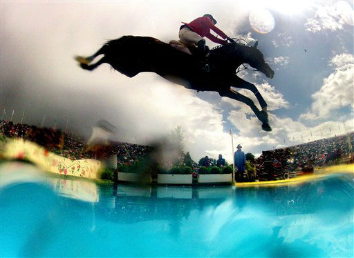 In this photo made using a fisheye lens, Jaime Azcarraga, of Mexico, rides his horse Gangster, in the equestrian show jumping team competition at the 2012 Summer Olympics, Sunday, Aug. 5, 2012, in London. &#40;AP Photo&#47;David Goldman&#41; <span class=meta>(AP Photo&#47; David Goldman)</span>