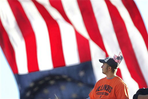 An Illinois football fans wears American flags in his hat and an American flag flies above Memorial Stadium in honor of American veterans during the NCAA college football game between Illinois and Minnesota Saturday, Nov. 10, 2012 in Champaign, Ill. &#40;AP Photo&#47;Seth Perlman&#41; <span class=meta>(AP Photo&#47; Seth Perlman)</span>