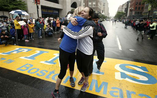 Rachel, left, and Pam Vingsness of Newton, Mass., hug each other after crossing the finish line as runners who were unable to finish the Boston Marathon on April 15 because of the bombings were allowed to finish the last mile of the race in Boston, Saturday, May 25, 2013. &#40;AP Photo&#47;Winslow Townson&#41; <span class=meta>(AP Photo&#47; Winslow Townson)</span>