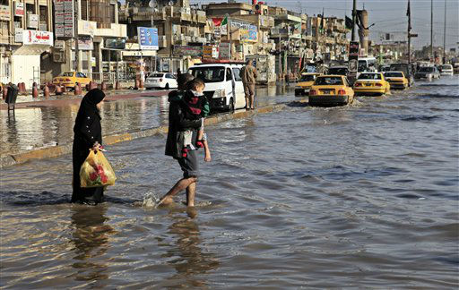 An Iraqi family make their way through flood water, after heavy rain fell in Baghdad, Iraq, Wednesday, Dec. 26, 2012. An unusually heavy rainstorm has collapsed shoddy houses in Iraq, killing a woman and several children, police and health officials said Wednesday. &#40;AP Photo&#47;Karim Kadim&#41; <span class=meta>(AP Photo&#47; Karim Kadim)</span>