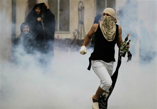 "<div class=""meta ""><span class=""caption-text "">A masked Bahraini anti-government protester carrying petrol bombs confronts riot police firing tear gas to disperse participants in a mourning procession for a teenager whose death the opposition blames on police in Muharraq, Bahrain,  Tuesday, Nov. 13, 2012. A drawing on the wall is a depiction of the now-demolished monument that stood at the hub of last year's pro-democracy uprising. (AP Photo/Hasan Jamali) (AP Photo/ Hasan Jamali)</span></div>"