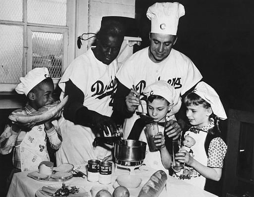 "<div class=""meta ""><span class=""caption-text "">Brooklyn Dodgers Pee Wee Reese, right, and Jackie Robinson, left, prepare a nutritious lunch of soup, hero sandwiches, milk and fruit for a group of Brooklyn youngers at the Ebbetts Field snack bar, in New York, May 3, 1956. It was part of a drive to interest school kids in preparing and eating nutritious well balanced lunches. (AP Photo) (AP Photo/ XKV)</span></div>"