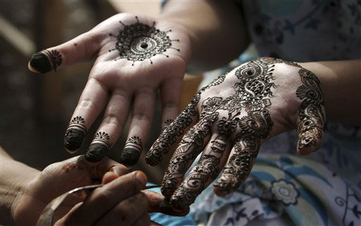 "<div class=""meta ""><span class=""caption-text "">A Pakistani girl gets her hands painted with henna in preparation for the upcoming Eid al-Fitr festival, in Karachi, Pakistan, Saturday, Aug. 18, 2012. Eid al-Fitr marks the end of the holy month of Ramadan. (AP Photo/Fareed Khan)</span></div>"