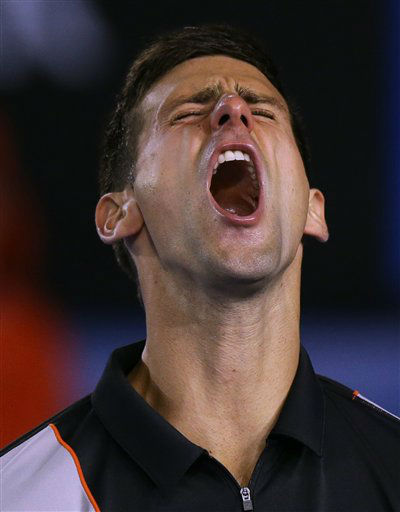 Novak Djokovic of Serbia celebrates a point won against Stanislas Wawrinka of Switzerland in the fourth set of their quarterfinal at the Australian Open tennis championship in Melbourne, Australia, Tuesday, Jan. 21, 2014.(AP Photo/Aaron Favila)