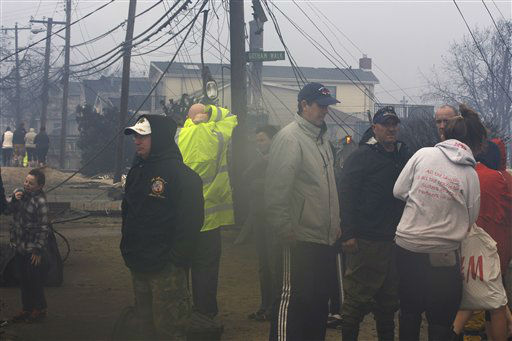 People assess damage caused by a fire at Breezy Point in the New York City borough of Queens Tuesday, Oct. 30, 2012. The fire destroyed between 80 and 100 houses Monday night in an area flooded by the superstorm that began sweeping through earlier. &#40;AP Photo&#47;Frank Franklin II&#41; <span class=meta>(AP Photo&#47; Frank Franklin II)</span>