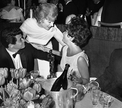 Greer Garson, center, a nominee for the best actress award, pauses to congratulate the winner, Elizabeth Taylor, right, at a supper party following the previous nights Academy Award presentation. At left is Taylors husband Eddie Fisher. &#40;AP Photo&#47;David F. Smith&#41; <span class=meta>(AP Photo&#47; David F. Smith)</span>