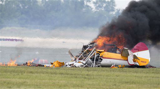 Smoke rises from a stunt plane after it crashed during a wing walker&#39;s performance at the Vectren Air Show, Saturday, June 22, 2013, in Dayton, Ohio. The crash killed the pilot and the wing walker instantly, authorities said. &#40;AP Photo&#47;Thanh V Tran&#41; MANDATORY CREDIT DOMESTIC USE ONLY. FOR INTERNATIONAL USE CONTACT AP IMAGES <span class=meta>(AP Photo&#47; Thanh V Tran)</span>