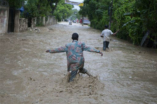 Residents wade through a flooded street caused by heavy rains from Hurricane Sandy in Port-au-Prince, Haiti, Thursday, Oct. 25, 2012. Hurricane Sandy rumbled across mountainous eastern Cuba and headed toward the Bahamas on Thursday as a Category 2 storm, bringing heavy rains and blistering winds.  &#40;AP Photo&#47;Dieu Nalio Chery&#41; <span class=meta>(AP Photo&#47; Dieu Nalio Chery)</span>