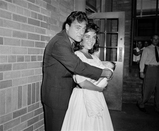 While poppa Mike Todd puts out a protecting hand, little Liza Todd leaves Harkness Pavilion, New York City, on Sept. 3, 1957 in the arms of her mother, actress Elizabeth Taylor.  The Todds came to New York from their Connecticut home to pick up Liza, born prematurely on August 6. &#40;AP Photo&#47;Tom Fitzsimmons&#41; <span class=meta>(AP Photo&#47; Tom Fitzsimmons)</span>
