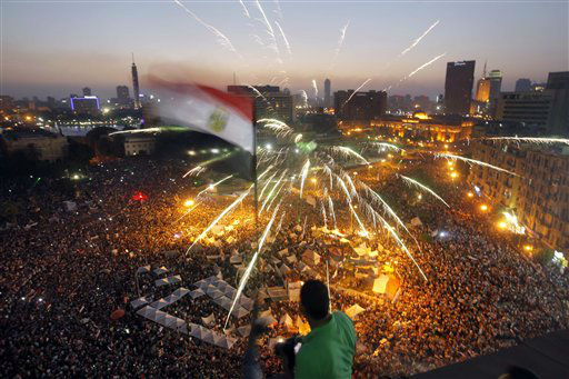 "<div class=""meta image-caption""><div class=""origin-logo origin-image ""><span></span></div><span class=""caption-text"">An Egyptian protester waves a national flag as Egyptians gather in Tahrir Square during a demonstration against President Mohammed Morsi in Cairo, Sunday, June 30, 2013. Hundreds of thousands of opponents of Egypt's Islamist president poured out onto the streets in Cairo and across much of the nation Sunday, launching an all-out push to force Mohammed Morsi from office on the one-year anniversary of his inauguration. Fears of violence were high, with Morsi's Islamist supporters vowing to defend him. (AP Photo/Amr Nabil) (AP Photo/ Amr Nabil)</span></div>"