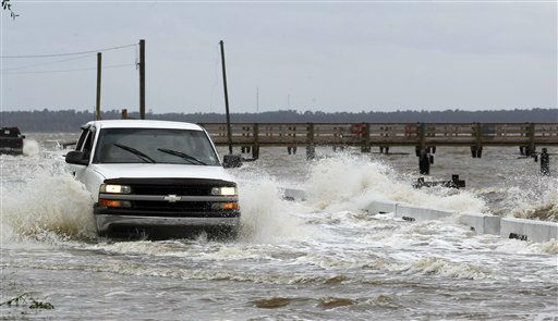 "<div class=""meta ""><span class=""caption-text "">A motorist drives through a flooded street as waves ahead of Isaac break over the road way  Tuesday, Aug. 28, 2012, in Bay St. Louis, Miss. The Gulf Coast braced for the landfall of Hurricane Isaac late, hunkering down behind boarded-up windows with stockpiles of food and water as wind-driven rain lashed bayous and beaches. New Orleans calmly waited out another storm on the eve of Hurricane Katrina's seventh anniversary, hoping the city's strengthened levees will hold. (AP Photo/John Bazemore) (AP Photo/ John Bazemore)</span></div>"