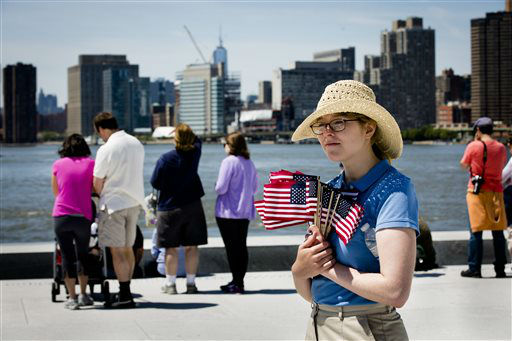 Park ranger Victoria Thompson holds American flags as visitors view the Manhattan skyline after a Memorial Day wreath laying at the Franklin D. Roosevelt Four Freedoms Park on Roosevelt Island, Monday, May 27, 2013, in New York. &#40;AP Photo&#47;John Minchillo&#41; <span class=meta>(AP Photo&#47; John Minchillo)</span>