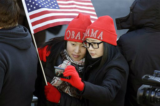 Khongorzul Battsengel, left, and Ariunbolor Davaatsogt both from Mongolia, take a picture of themselves as they wait for President Barack Obama in the 57th Presidential Inaugural Parade on Pennsylvania Avenue, Monday, Jan. 21, 2013 in Washington. Thousands marched during the 57th Presidential Inauguration parade after the ceremonial swearing-in of Obama. &#40;AP Photo&#47;Alex Brandon&#41; <span class=meta>(AP Photo&#47; Alex Brandon)</span>
