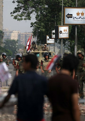 Supporters of ousted President Mohammed Morsi protest as army soldiers guard at the Republican Guard building in Nasr City, Cairo, Egypt, Tuesday, July 9, 2013. Egyptian security forces killed dozens of supporters of Egypt&#39;s ousted president in one of the deadliest single episodes of violence in more than two and a half years of turmoil. The toppled leader&#39;s Muslim Brotherhood called for an uprising, accusing troops of gunning down protesters, while the military blamed armed Islamists for provoking its forces. &#40;AP Photo&#47;Khalil Hamra&#41; <span class=meta>(AP Photo&#47; Khalil Hamra)</span>