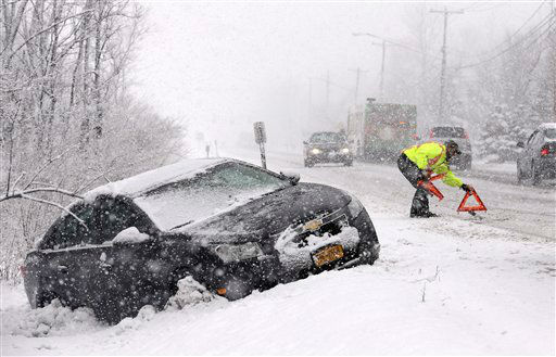 Tow truck operator Shawn Juhre sets up road safety reflectors before towing a car out of a ditch during a winter snow storm in Buffalo, N.Y., Friday, Feb. 8, 2013. Snow began falling across the Northeast on Friday, ushering in what was predicted to be a huge, possibly historic blizzard and sending residents scurrying to stock up on food and gas up their cars. The storm could dump 1 to 3 feet of snow from New York City to Boston and beyond. &#40;AP Photo&#47;David Duprey&#41; <span class=meta>(AP Photo&#47; David Duprey)</span>