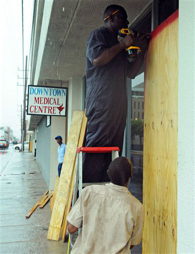 Workers board up businesses as Hurricane Sandy reaches Jamaica.