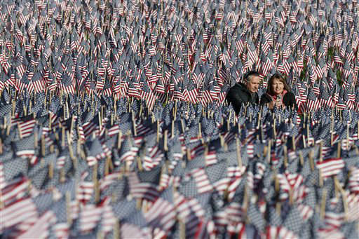 A couple photograph themselves amongst a sea of flags on Boston Common in Boston, Sunday, May 26, 2013. The flags were placed by the  Massachusetts Military Heroes Fund in memory of every fallen Massachusetts service member from the Civil War to the present. &#40;AP Photo&#47;Michael Dwyer&#41; <span class=meta>(AP Photo&#47; Michael Dwyer)</span>