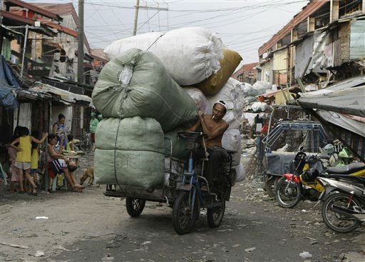 "<div class=""meta ""><span class=""caption-text "">A Filipino man negotiates his motorized bicycle along a dirt road as he brings loads of used plastics which he will sell at a junk shop in a poor district in Manila, Philippines, on Monday Dec. 3, 2012. Many survive on odd jobs in poor communities in the country, where nearly a third of the 90 million population wallow in poverty. (AP Photo/Aaron Favila) (AP Photo/ Aaron Favila)</span></div>"