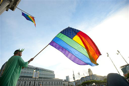 "<div class=""meta ""><span class=""caption-text "">Nikolas Lemos waves a rainbow flag outside San Francisco's City Hall shortly before a Supreme Court ruling cleared the way for same-sex marriage in California on Wednesday, June 26, 2013.  The justices issued two 5-4 rulings in their final session of the term. One decision wiped away part of a federal anti-gay marriage law that has kept legally married same-sex couples from receiving tax, health and pension benefits. The other was a technical legal ruling that said nothing at all about same-sex marriage, but left in place a trial court's declaration that California's Proposition 8 is unconstitutional.  (AP Photo/Noah Berger) (AP Photo/ Noah Berger)</span></div>"