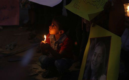A Palestinian boy holds a candle in front of a poster of Rachel Corrie, a pro-Palestinian activist who was killed by an Israeli bulldozer in Gaza in 2003, during a rally in solidarity with Rachael Corrie , in Rafah,  southern Gaza Strip, Wednesday, Aug. 29, 2012. An Israeli court on Monday rejected a lawsuit brought against the military by the parents of a U.S. activist crushed to death by an army bulldozer during a 2003 demonstration, ruling the army was not at fault for her death. The bulldozer driver has said he didn&#39;t see 23-year-old Rachel Corrie, who was trying to block the vehicle&#39;s path during a demonstration in the Gaza Strip against the military&#39;s demolition of Palestinian homes. The military deemed her March 2003 death to be accidental, but Corrie&#39;s parents were not satisfied by the army investigation and filed a civil lawsuit two years later. &#40;AP Photo&#47;Adel Hana&#41; <span class=meta>(AP Photo&#47; Adel Hana)</span>