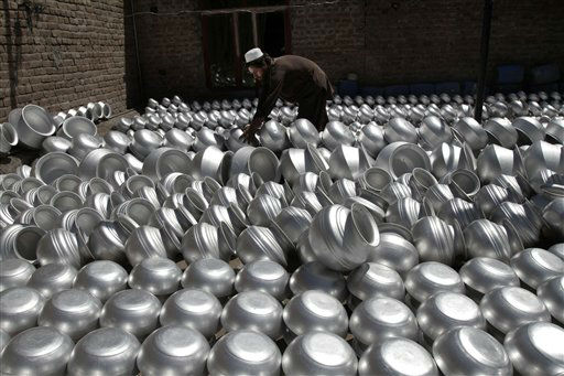An Afghan laborer arranges pots at an aluminum factory, on Surkh Rod district of Jalalabad east of Kabul, Afghanistan, Wednesday, June 5, 2013. Men working at the factory earn an average of 400 AFN &#40;&#36; 7.28 cents&#41; per day. &#40;AP Photo&#47;Rahmat Gul&#41; <span class=meta>(AP Photo&#47; Rahmat Gul)</span>