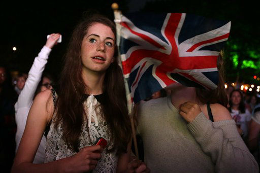 Visitors at a park hold a British flag during the live telecast of the Opening Ceremony of the 2012 Summer Olympics, Friday, July 27, 2012, in London. &#40;AP Photo&#47;Ng Han Guan&#41; <span class=meta>(AP Photo&#47; Ng Han Guan)</span>