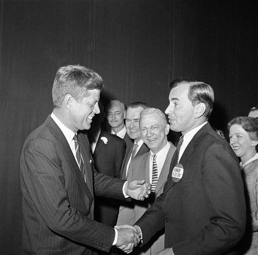 President-elect John F. Kennedy looks at a Button that Gore Vidal wears as he meets visits backstage after attending Broadway show ?The best man? at the morocco theatre in New York, Dec. 6, 1960. In center is lee Tracy and next to Tracy is Frank Lovejoy, co-stars in the show. Others are unidentified. Play, written by Vidal, has political theme. Kennedy is in New York to meet U.N. secretary general Dag Hammarskjold. Vidal ran unsuccessfully for congress in recent election. &#40;AP Photo&#41; <span class=meta>(AP Photo&#47; Anonymous)</span>