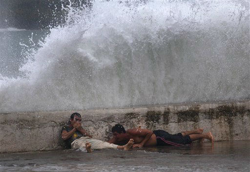 Men lay behind the seawall as waves brought by Tropical Storm Isaac splash over them in Baracoa, Cuba, Saturday, Aug. 25, 2012. Tropical Storm Isaac pushed into Cuba on Saturday after sweeping across Haiti&#39;s southern peninsula. Isaac&#39;s center made landfall just before midday near the far-eastern tip of Cuba. &#40;AP Photo&#47;Ramon Espinosa&#41; <span class=meta>(AP Photo&#47; Ramon Espinosa)</span>