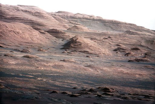 In this image released by NASA on Monday, Aug. 27, 2012, a chapter of the layered geological history of Mars is laid bare in this color image from NASA&#39;s Curiosity rover showing the base of Mount Sharp, the rover&#39;s eventual science destination. The image is a portion of a larger image taken by Curiosity&#39;s 100-millimeter Mast Camera on Aug. 23, 2012. Scientists enhanced the color in one version to show the Martian scene under the lighting conditions we have on Earth, which helps in analyzing the terrain. The pointy mound in the center of the image, looming above the rover-sized rock, is about 1,000 feet &#40;300 meters&#41; across and 300 feet &#40;100 meters&#41; high. &#40;AP Photo&#47;NASA&#47;JPL-Caltech&#47;MSSS&#41; <span class=meta>(AP Photo&#47; Uncredited)</span>