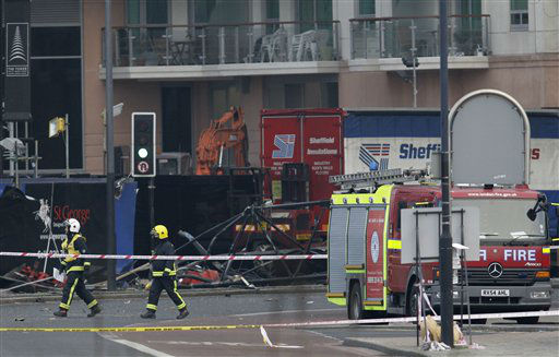 "<div class=""meta ""><span class=""caption-text "">Firefighters walk pass the section of damaged crane on the ground after a helicopter crashed into the crane on top of a building in central London, Wednesday Jan. 16, 2013. Police say two people were killed when a helicopter crashed Wednesday during rush hour in central London after apparently hitting a construction crane on top of a building. (AP Photo/Sang Tan) (AP Photo/ Sang Tan)</span></div>"