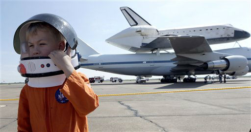 Joey Morrison adjusts his space helmet after watching the shuttle aircraft carrier with space shuttle Endeavour atop, land Wednesday, Sept. 19, 2012, at Ellington Field in Houston. Endeavour is making a final trek across the country to the California Science Center in Los Angeles, where it will be permanently displayed. &#40;AP Photo&#47;David J. Phillip <span class=meta>(AP Photo&#47; David J. Phillip)</span>