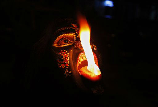 In this, Sunday, Oct. 21, 2012 photo, an Indian performer disguised as Hindu Goddess Kali performs with fire during Navratri festival in Allahabad, India. Navratri or the festival of nine nights is an annual Hindu festival of worship and dance. &#40;AP Photo&#47;Rajesh Kumar Singh&#41; <span class=meta>(AP Photo&#47; Rajesh Kumar Singh)</span>