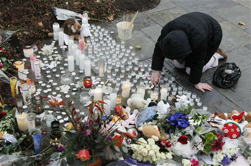 "<div class=""meta ""><span class=""caption-text "">A woman pays respects at a memorial outside of St. Rose of Lima Roman Catholic Church, Sunday, Dec. 16, 2012, in Newtown, Conn. On Friday, a gunman allegedly killed his mother at their home and then opened fire inside the Sandy Hook Elementary School in Newtown, killing 26 people, including 20 children. (AP Photo/Julio Cortez) (AP Photo/ Julio Cortez)</span></div>"
