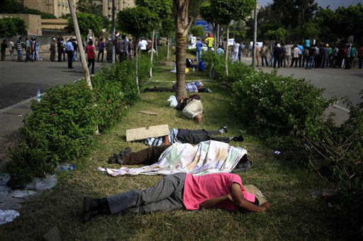 "<div class=""meta ""><span class=""caption-text "">Supporters of ousted President Mohammed Morsi sleep as they protest at the Republican Guard building in Nasr City, Cairo, Egypt, Tuesday, July 9, 2013. Egyptian security forces killed dozens of supporters of Egypt's ousted president in one of the deadliest single episodes of violence in more than two and a half years of turmoil. The toppled leader's Muslim Brotherhood called for an uprising, accusing troops of gunning down protesters, while the military blamed armed Islamists for provoking its forces. (AP Photo/Khalil Hamra) (AP Photo/ Khalil Hamra)</span></div>"