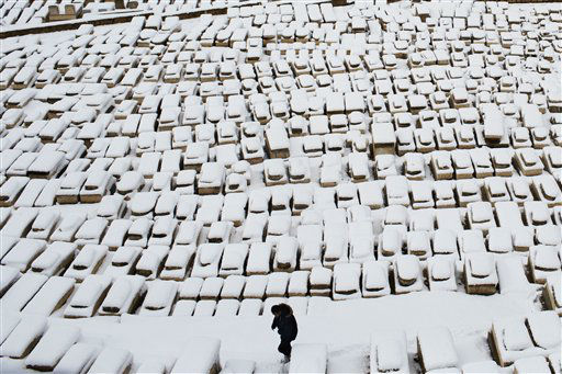 A man walks through tombs covered by snow on the Mount of Olives, in Jerusalem, Thursday, Jan. 10, 2013. Stormy weather conditions continued on Thursday with snow, torrential rains and strong winds across the region. &#40;AP Photo&#47;Bernat Armangue&#41; <span class=meta>(AP Photo&#47; Bernat Armangue)</span>
