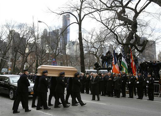 A casket containing the body of former New York City Mayor Ed Koch is loaded into a hearse while city employees, politicians, media and others look on after his funeral in New York, Monday, Feb. 4, 2013. Koch was remembered as the quintessential New Yorker during a funeral that frequently elicited laughter, recalling his famous one-liners and amusing antics in the public eye. Koch died Friday of congestive heart failure at age 88. &#40;AP Photo&#47;Seth Wenig&#41; <span class=meta>(AP Photo&#47; Seth Wenig)</span>